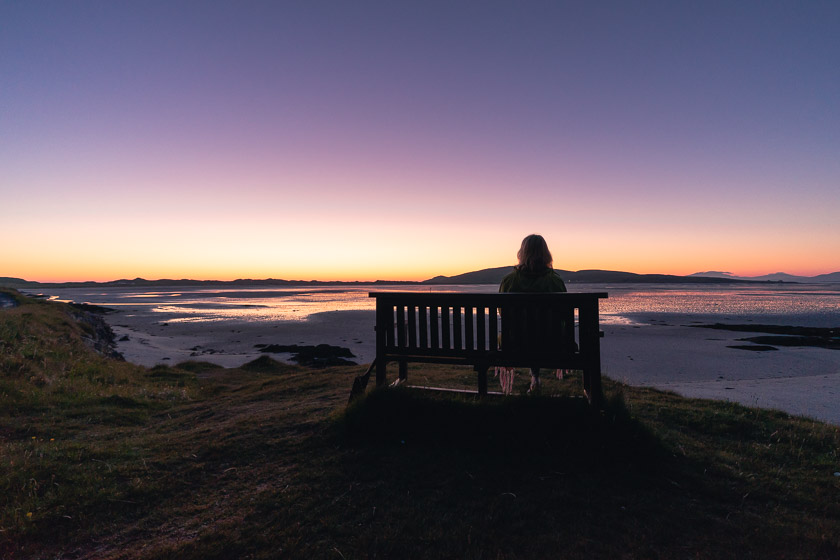 A woman sits on a bench looking out over Tràigh Mhòr on the Isle of Barra at sunset.