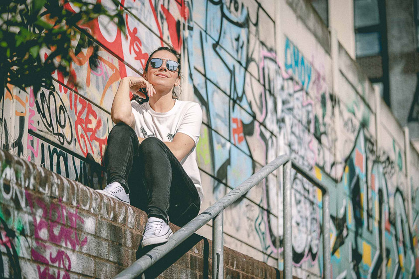 A model wearing sunglasses sits on a wall covered in colourful graffiti