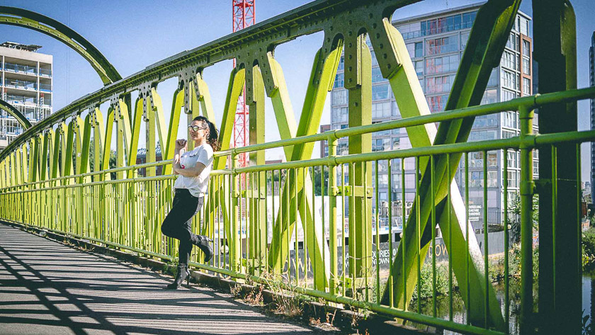 A model stands on a green iron bridge in the sunshine