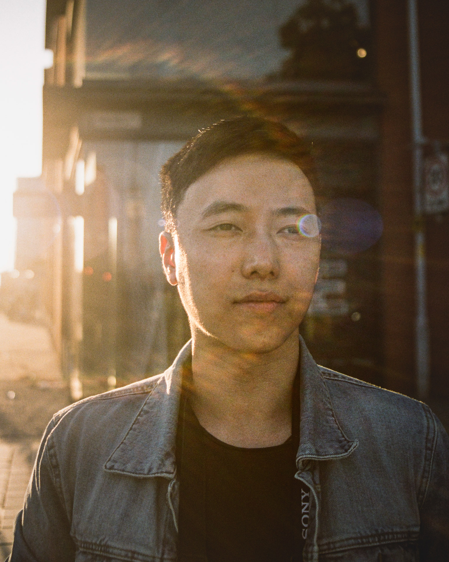 A Chinese man looks past the camera to the distance, with a sunburst across his face.