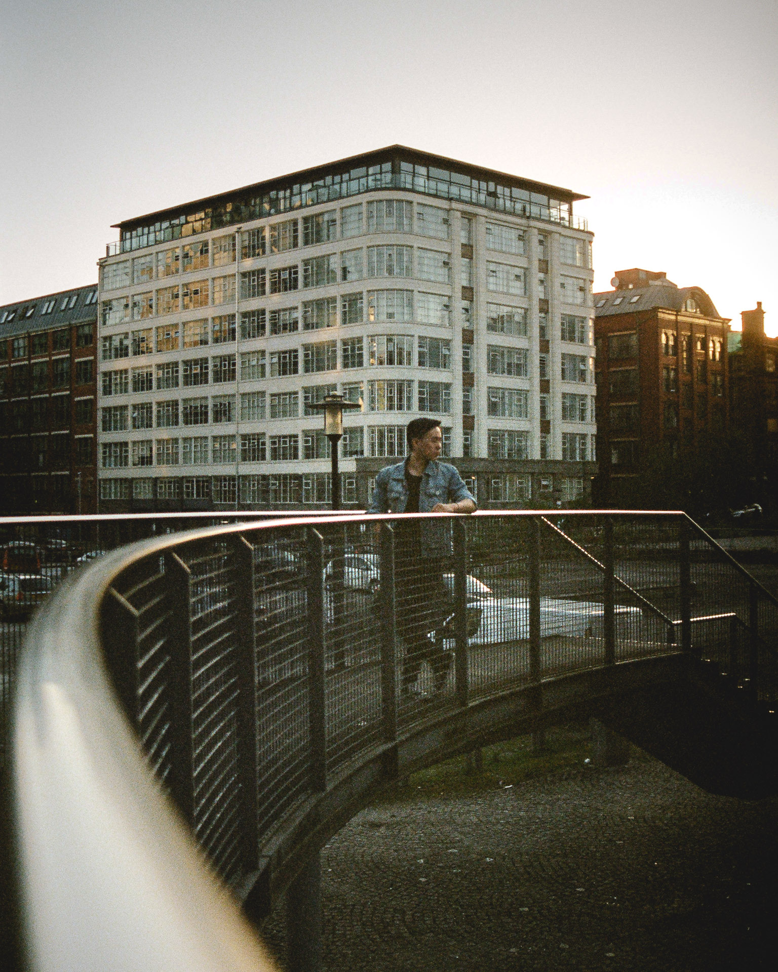 A man stands on a curved bridge in front of a white art-deco apartment block.