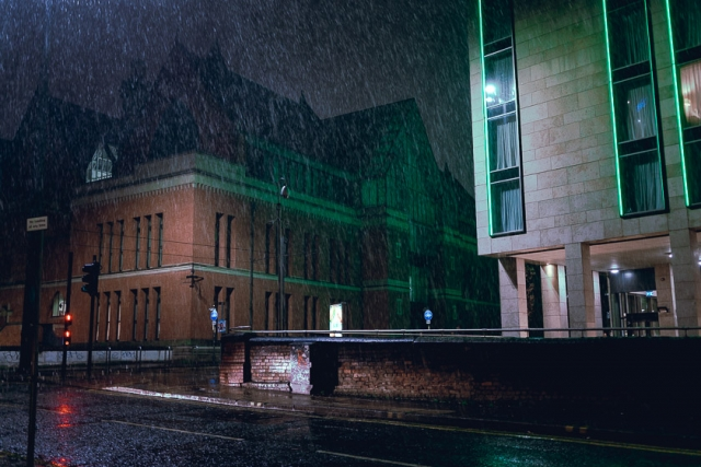 The green glow of the Holiday Inn illuminates the falling rain in Manchester