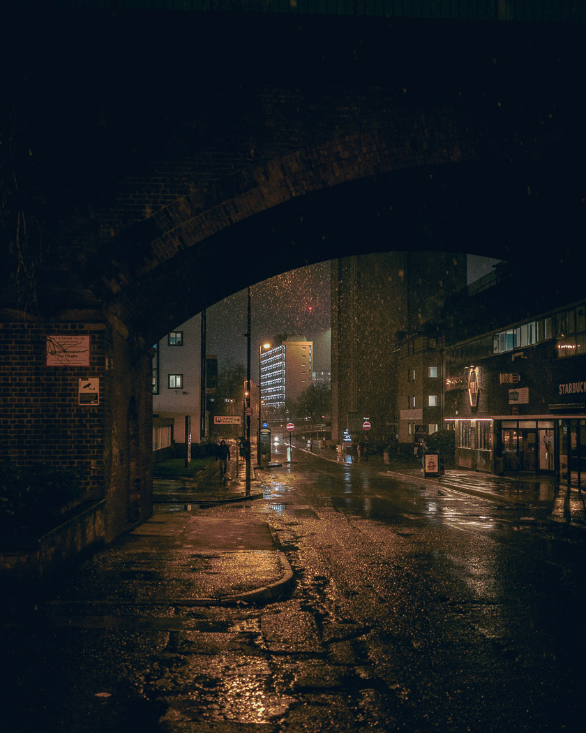 A nighttime view under a railway arch at the snow falling in Manchester