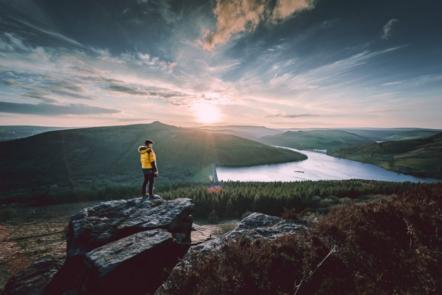 A man stands on a rock overlooking Ladybower reservoir in the Peak District.