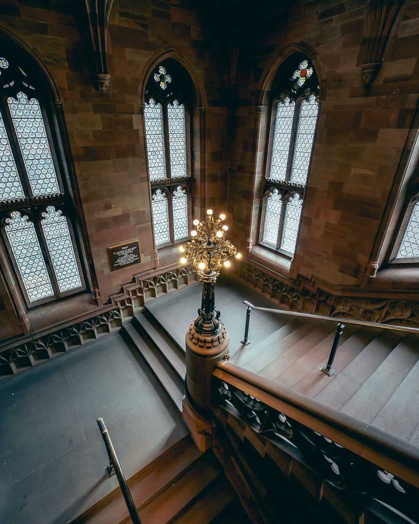 A grand stone staircase turns around an elegant light, flanked by large gothic windows