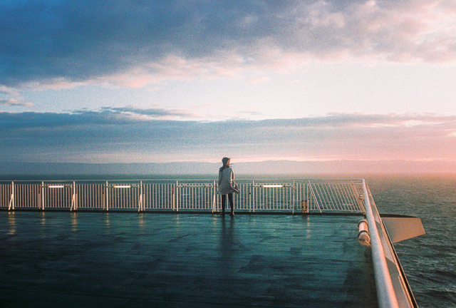 A woman stands on the deck of a ferry at sunset, looking out to sea
