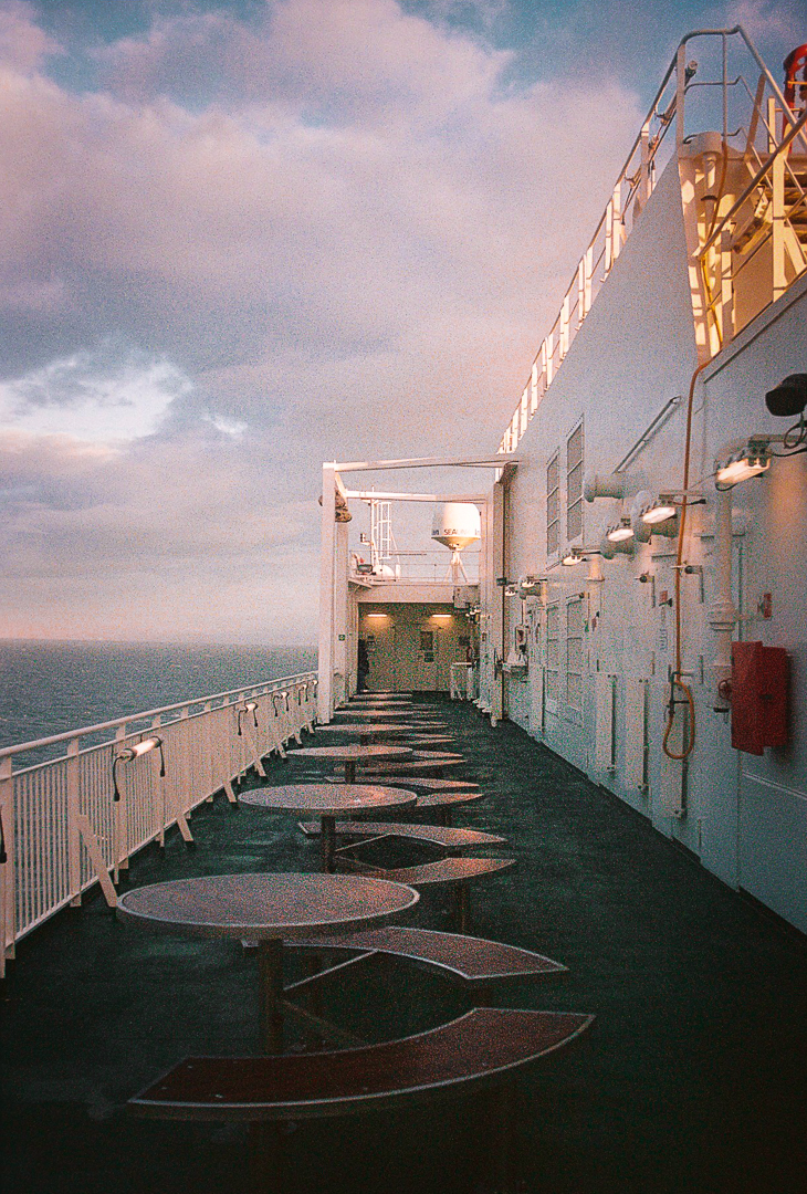Outside picnic tables on a ferry at sunset